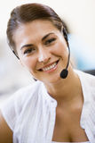 Woman wearing headset indoors smiling Royalty Free Stock Photo
