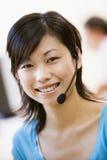 Woman wearing headset indoors smiling Stock Image