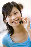 Woman wearing headset indoors smiling Royalty Free Stock Photography