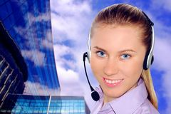 Woman wearing headset in office;could be reception. Woman wearing headset in office; could be receptionist on business architecture background royalty free stock photography
