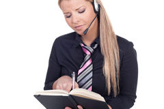 Woman wearing a headset taking notes Royalty Free Stock Photo