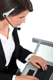 Woman wearing a headset typing at a keyboard Stock Images