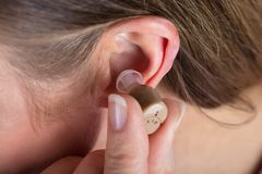 Woman Wearing Hearing Aid. Close-up Photo Of Woman Wearing Hearing Aid stock photography