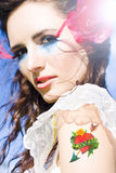 Woman Wearing Heart On Sleeve. Woman With Creative Makeup And A Red Rose In Her Hair Wears A Love Heart Tattoo On Her Arm Symbolizing The Metaphor Wearing Your Royalty Free Stock Photo