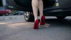 Woman wearing heels getting into parked car stock video footage