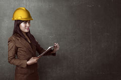 Woman wearing helmet holding clipboard Royalty Free Stock Photo