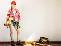 Woman wearing helmet, toolbelt about to drill wall Royalty Free Stock Images