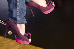 Woman wearing high heels sitting on bar stool. Close up of a woman wearing purple shoes with high heels sitting on bar stool Stock Photo