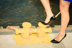 Woman wearing high heels, standing on marina bolt Royalty Free Stock Images