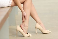 Woman wearing high heels touching painful legs. Close up of a woman wearing high heels touching painful legs in the street stock photography