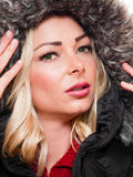 Woman wearing hood. A image of a attractive woman wearing a black coat wuth the fur lined hood pulled up royalty free stock image