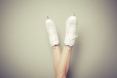 Woman wearing ice skates against a wall Royalty Free Stock Images