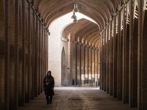 Woman wearing the islamic veil walking in a street of the covered bazaar of Isfahan, one of the major landmarks of the city stock photo