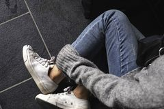 A woman wearing jean and white sneakers touching her leg while sitting on the floor. Top view image of a woman wearing jean and white sneakers touching her leg royalty free stock images