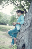 Woman  wearing jeans and a denim jacket. She relax in the holida. Y and her lifestyle at the public park. She leaned against a tree Stock Photos