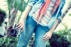 Woman wearing jeans and denim shirt holding camera outside Royalty Free Stock Image