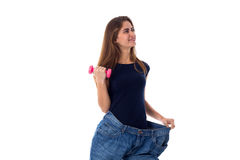 Woman wearing jeans of much bigger size and holding a dumbbell Stock Image