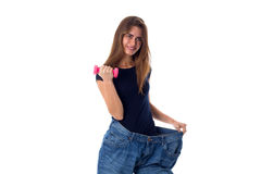 Woman wearing jeans of much bigger size and holding a dumbbell Stock Photos