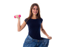 Woman wearing jeans of much bigger size and holding a dumbbell Royalty Free Stock Photo