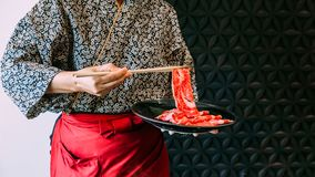 Woman wearing kimono holding rare slice Wagyu A5 beef by chopsticks for boiling in Sukiyaki hot pot