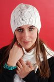 Woman wearing knit hat. Portrait of a pretty woman wearing a white knit hat and scarf.  Red background Stock Photography