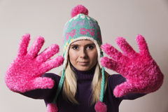 Woman wearing a knitted cap stretching her hands in front of her Royalty Free Stock Photography