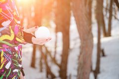 Woman wearing a knitted scarf and gloves holding a snowball. In winter forest royalty free stock photo