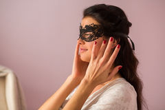 Woman wearing lace mask. Girl with dark hair. Recognize the beauty stock image