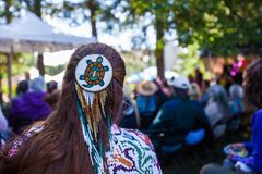 Woman is wearing a large turtle beaded hair pin and colorful native clothing stock images