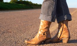 Woman wearing leather boots. Standing next to the road Royalty Free Stock Images