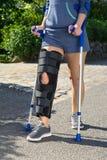 Woman wearing a leg brace walking on crutches Stock Photo