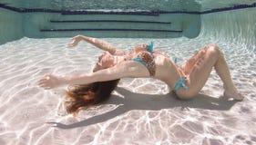 A woman wearing a leopard pring swimsut underwater. Stock Image