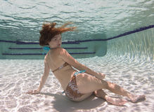 A woman wearing a leopard pring swimsut underwater. Stock Images