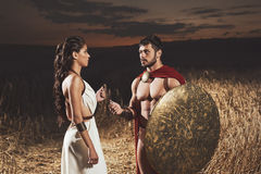 Woman wearing like greece giving amulet to man like spartan. Royalty Free Stock Image