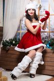 Woman wearing like Santa`s helper. Posing with christmas toy near the window stock photography