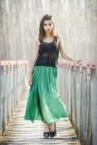 Woman wearing long dress in a rural bridge Stock Image