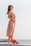 Woman wearing long light pink dress on jetty Royalty Free Stock Photo