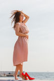 Woman wearing long light pink dress on jetty Stock Images