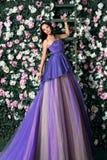 Woman wearing long purple dress posing in the flowered garden Stock Image