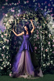 Woman Wearing Long Purple Dress Posing In The Flowered Garden Stock Photography