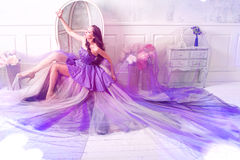 Woman wearing long purple dress posing in studio interior Stock Photography
