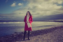 Worried woman on beach. A woman wearing a long red coat on a beach with a worried look on her face Stock Photo