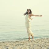 Woman wearing long white dress having fun on a seacoast. Stock Image