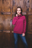 Woman wearing magenta sweatshirt in front of wooden wall. Young woman wearing blank magenta sweatshirt with area for your logo or design, mock-up of template Stock Photography