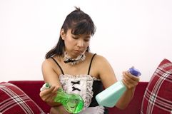 Woman wearing maid costume compares products Stock Photography