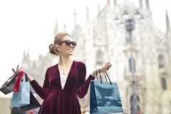Woman Wearing Maroon Velvet Plunge-neck Long-sleeved Dress While Carrying Several Paper Bags Photography Stock Photo