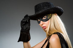 Woman wearing mask against. Dark background Royalty Free Stock Photography