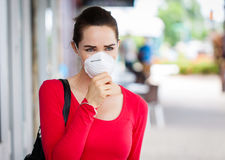 Woman wearing mask coughing Stock Photo