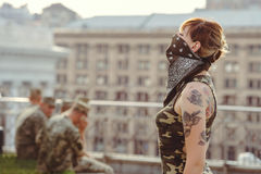 Woman wearing a mask and military clothing for protest, freedom of speech and independence, military aggression and conflicts, so stock photography