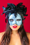 Woman wearing a masquerade mask red background Royalty Free Stock Photo